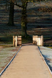 Frozen Path Leading to a Bridge. Shot taken on an early frosty morning on a country park path, leading to a sunlit bridge Royalty Free Stock Image