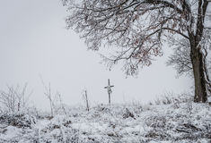 Frozen peace. Winter cemetery scene with a cross in the snow Stock Photo