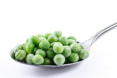 Frozen peas. On a spoon Royalty Free Stock Images