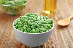 Frozen peas in bowl. On wooden background Stock Photos