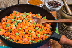Frozen peas and carrots for cooking on a pan Royalty Free Stock Image
