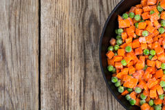 Frozen peas and carrots for cooking on a pan Royalty Free Stock Photos