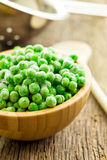 Frozen peas in wooden bowl Royalty Free Stock Image