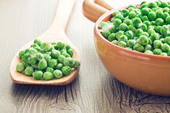 Frozen peas on wooden spoon Royalty Free Stock Photography