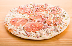 Frozen Pepperoni Pizza on Wood Cutting Board royalty free stock photos