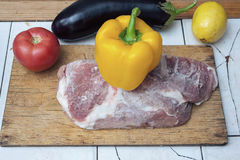 Frozen piece of meat on a wooden cutting board and yellow bell pepper, red tomato and eggplant on the table. Royalty Free Stock Photos