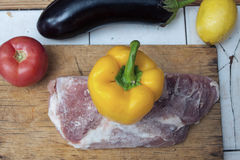 Frozen piece of meat on a wooden cutting board and yellow bell pepper, red tomato and eggplant on the table. Stock Image