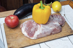 Frozen piece of meat on a wooden cutting board and yellow bell pepper, red tomato and eggplant on the table. Royalty Free Stock Images