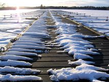 A frozen pier. A winter view on a frozen lake and a desolate pier lit by late afternoon sun. Low season for boat activities Stock Photo