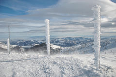 Frozen pillars. Three frozen iron pillars, completely covered by snow and icicles and mountain winter landscape under blue sky with some high clouds Royalty Free Stock Photography