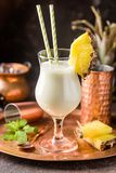 Frozen Pina Colada Cocktail. Homemade frozen Pina Colada cocktail with rum, coconut milk and pineapple garnish over black background Royalty Free Stock Photos