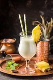 Frozen Pina Colada Cocktail. Homemade frozen Pina Colada cocktail with rum, coconut milk and pineapple garnish over black background Royalty Free Stock Images