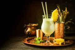 Frozen Pina Colada Cocktail. Homemade frozen Pina Colada cocktail with rum, coconut milk and pineapple garnish over black background Stock Image