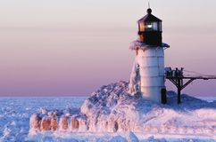 Frozen Pink Lighthouse on Lake Michigan stock photo