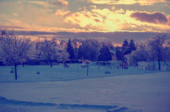 Frozen Playground After an Ice Storm - Retro. The sun setting behind some clouds over a frozen park landscape with an icy playground in the distance after an ice Stock Photo