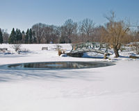 Frozen pond and bridge. A bridge over a frozen snow covered pond and stream stock image