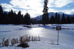 Frozen Pond in Mountain Resort. Snow covered frozen lake in beautiful mountain location Royalty Free Stock Image