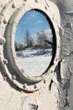 Frozen porthole on the white ships wall. Royalty Free Stock Photo