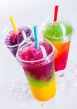 Frozen Rainbow Slush Drinks Chilling on Ice. Still Life Close Up of Colorful Rainbow Layered Frozen Fruit Slush Drinks Arranged on Ice Covered White Surface in Royalty Free Stock Photography