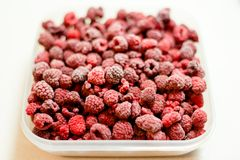 Frozen raspberries. In a plastic box on white background Stock Photo