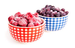 Frozen raspberries and bilberries. In the bowl, on a white background Stock Photo