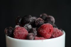 Frozen raspberries and blueberries on a dark background. Close up Stock Images