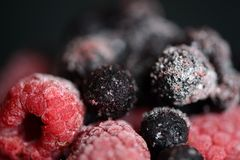 Frozen raspberries and blueberries on a dark background. Close up Stock Photos