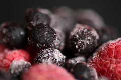 Frozen raspberries and blueberries on a dark background. Close up Royalty Free Stock Photos