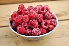 Frozen raspberries in a bowl. On table Stock Images
