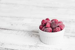 Frozen raspberries in a ceramic cup on on the light wooden background stock photography