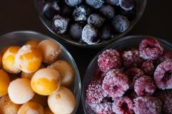 Frozen raspberries, currants and cherry plums. Various fruits from the freezer royalty free stock images