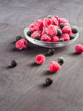 Frozen raspberries in a glass saucer. Frost on the berries. Stock Photo