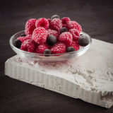 Frozen raspberries in a glass saucer. Frost on the berries. Dark background Royalty Free Stock Photo
