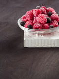 Frozen raspberries in a glass saucer. Frost on the berries. Dark background Royalty Free Stock Image