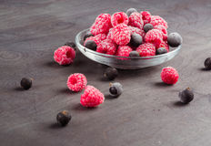 Frozen raspberries in a glass saucer. Frost on the berries. Royalty Free Stock Photography