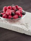 Frozen raspberries in a glass saucer. Frost on the berries. Stock Photos