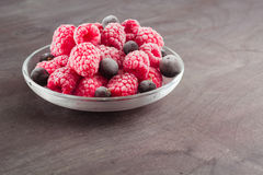 Frozen raspberries in a glass saucer. Frost on the berries. Royalty Free Stock Photos