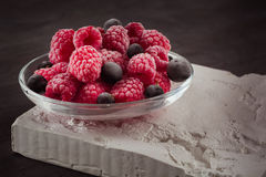 Frozen raspberries in a glass saucer. Frost on the berries. Royalty Free Stock Images