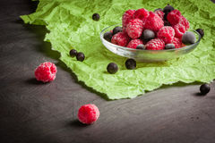 Frozen raspberries in a glass saucer. Green crumpled paper. Frost on the berries. Stock Photo