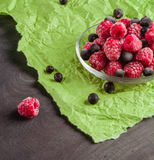 Frozen raspberries in a glass saucer. Green crumpled paper. Frost on the berries. Royalty Free Stock Photo