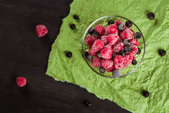 Frozen raspberries in a glass saucer. Green crumpled paper. Frost on the berries. Stock Photos