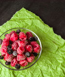 Frozen raspberries in a glass saucer. Green crumpled paper. Frost on the berries. Royalty Free Stock Image