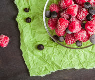 Frozen raspberries in a glass saucer. Green crumpled paper. Frost on the berries. Royalty Free Stock Photos