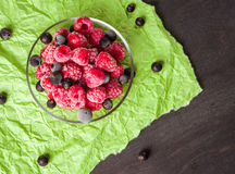 Frozen raspberries in a glass saucer. Green crumpled paper. Frost on the berries. Stock Photography