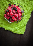 Frozen raspberries in a glass saucer. Green crumpled paper. Frost on the berries. Stock Images