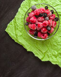 Frozen raspberries in a glass saucer. Green crumpled paper. Frost on the berries. Royalty Free Stock Photography