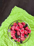 Frozen raspberries in a glass saucer. Green crumpled paper. Frost on the berries. Stock Image