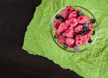 Frozen raspberries in a glass saucer. Green crumpled paper. Frost on the berries. Royalty Free Stock Images