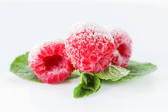 Frozen raspberries with mint leaves on white. Frozen raspberries macro with mint leaves and ice  on white background Royalty Free Stock Image