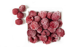 Frozen raspberries in a white porcelain dish Royalty Free Stock Images